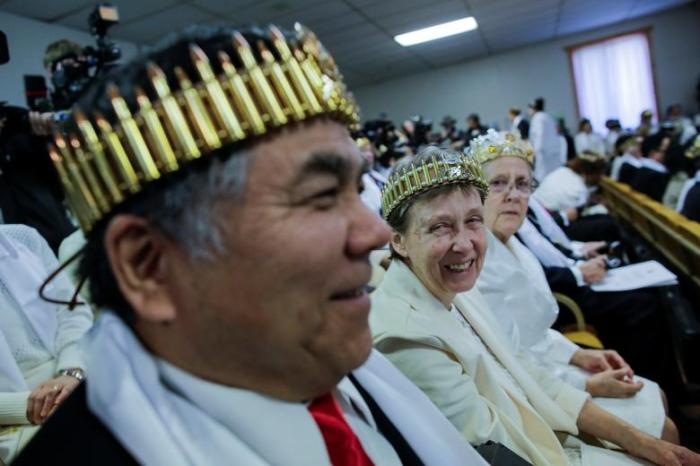 A couple wearing bullet crowns sit with their AR-15-style rifles in their cases, as people attend a blessing ceremony at the Sanctuary Church in Newfoundland